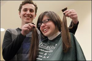 Boyfriend Blake Weible, 23, left, holds the hair of Dakota Lause after the first cuts were made before her head is fully shaved Sunday at BGSU.