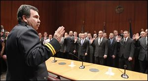 Toledo Fire and Rescue Department Battalion Chief Dave Dauer administers the oath of office to 43 new fire recruits a during a ceremony at One Government Center.
