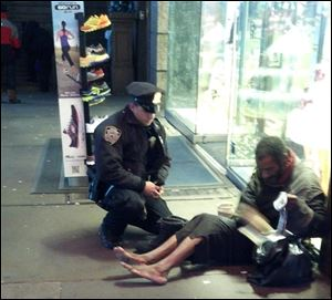 This photo provided by Jennifer Foster shows New York City Police Officer Larry DePrimo presenting a barefoot homeless man in New York's Time Square with boots on Nov. 14.