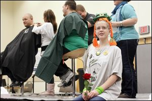 Connie Christiansen, a sixth-grader at Perrysburg Junior High School, sits on the stage after having her head shaved for a fund raiser for St. Baldrick's Foundation, which funds childhood cancer research grants.