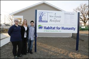 Christina Fisher flanked by her children left Alexis Sting, 17,  and right George Sting, 14, in front of their new  Habitat for Humanity home in Rossford, Ohio.