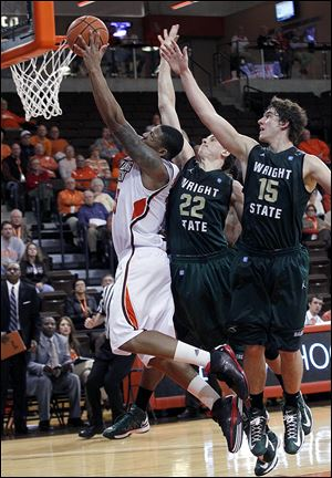 A'uston Calhoun, who led Bowling Green with19 points, goes to the basket against Wright State's Cole Darling (22) and Kendall Griffin (15) in Monday night's game at the Stroh Center.