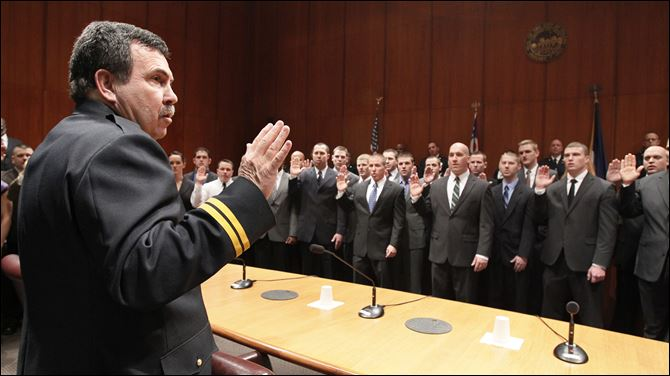 CTY swearingin04p Toledo Fire and Rescue Department Battalion Chief Dave Dauer administers the oath of office to 43 new fire recruits a during a ceremony at One Government Center.