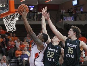 BGSU's A'uston Calhoun aims for the bucket with Wright's Cole Darling, #22, and Kendall Griffin on his back.