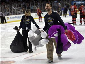Tony Bibler, a marketing promotion intern for the Toledo Walleye, helps with the larger stuffed animals that were thrown onto the ice rink during the annual Teddy Bear Toss.