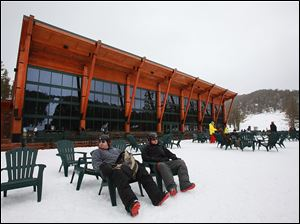 Snowboarders relax in chairs outside the Tamarack Lodge at Heavenly.