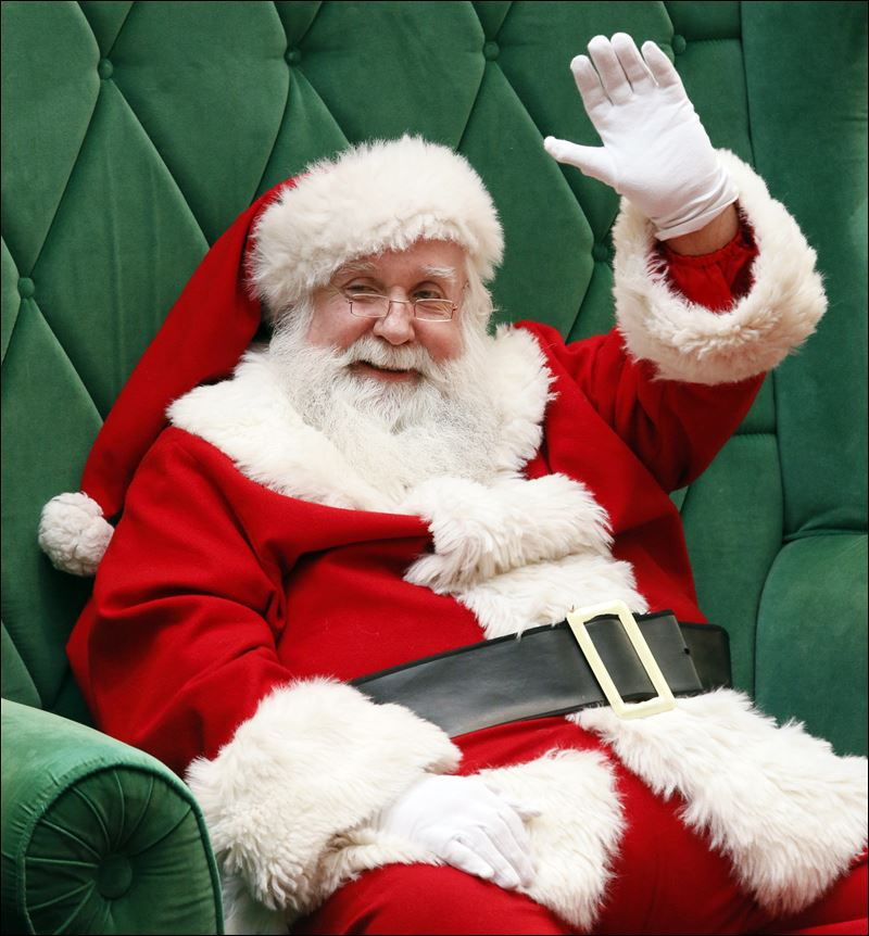 Santa Claus waves to people passing by in Westfield Franklin Park Mall ...