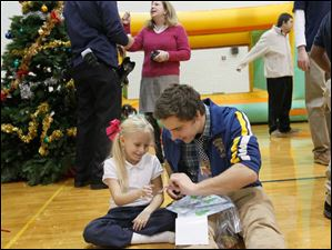 Mckenzie Hollers, 7, left, unwraps a gift with the help of Connor Lake, 18.