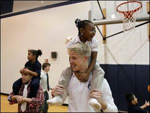 TyShaela Wright, 6, top center, cheers while receiving a piggy-back ride from Brogan Roback.