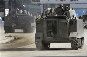Lebanese army soldiers patrol in armored vehicles after clashes erupted between pro and anti-Syrian regime gunmen in the northern port city of Tripoli, Lebanon.