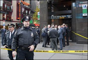 Uniformed and plainclothes police officers stand outside a New York subway station after a man was killed after falling into the path of a train.