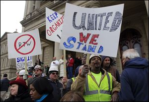 Union workers rally outside the Capitol in Lansing, Mich., as Senate Republicans introduced right-to-work legislation in the waning days of the legislative session. The outnumbered Democrats pledged to resist the proposal and said rushing it through the legislative system would poison the state's political atmosphere.