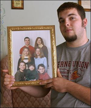 Matt Seager holds a family photo to show his twin sisters, Kimberly and Kathy, second row, who were killed in a crash on State Rt. 37. Matt Seager was driving the car, which was rear-ended