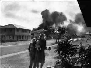 Officers' wives head to their quarters after investigating the sound of an explosion and seeing smoke in distance in Pearl Harbor, Hawaii. The two heard neighbor Mary Naiden, then an Army hostess who took this picture, exclaim