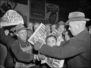 People buy newspapers reporting the Japanese attack on U.S. bases in the Pacific Ocean, at Times Square in New York.