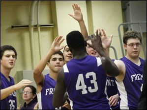 Fremont Ross' junior center Jarvis Jones is cheered on by his teammates as he exits the court at Clay Senior High School in Oregon. Fremont Ross won, 68-41.