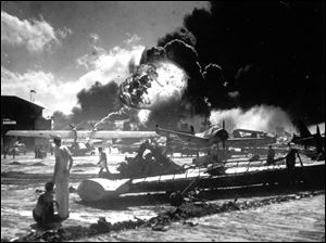 Sailors stand among wrecked airplanes at Ford Island Naval Air Station as they watch the explosion of the USS Shaw in the background, during the Japanese surprise attack on Pearl Harbor, Hawaii.