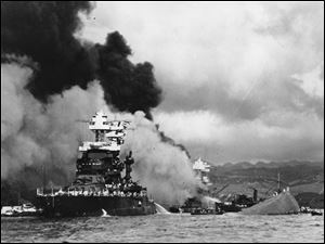 The battleship USS West Virginia, center, begins to sink after suffering heavy damage, while the USS Maryland, left, is still afloat in Pearl Harbor, Oahu, Hawaii. The capsized USS Oklahoma is at right.