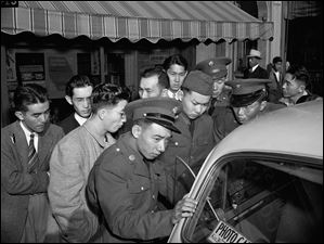 Young Japanese-Americans, including several Army selectees, gather around a reporter's car in the Japanese section of San Francisco.