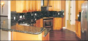 Mocha maple cabinets, Blue Volga black granite countertops, and stainless appliances make this kitchen completely on-trend. LEFT: The lighted art niche in the foyer greets visitors.