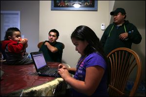Leslie Mendoza uses a laptop as her father, Felipe, right, his nephew Aaron Carillo and Carillo's son, Jayden, talk in the home htey rent in Aurora, Illinois. Some are turning foreclosed homes into investments by buying and turning them into rental properties.