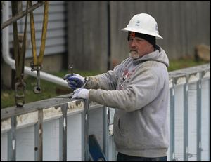 Bernie Griswold, Jr., of Clio, Mich., who works for Great Lakes Superior Walls, fastens foundation walls together on Chapin Street. Two houses there are to be finished in about  two months. They are to be sold to residents with low to moderate incomes.