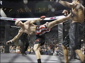 Eugene Barrett, left, kicks Matt Young during their fight at the Purgatory Fight Series 10 event.