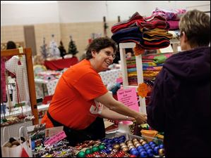 Lynn Kluczynski, of Sylvania, shows a customer her hand-made fabric