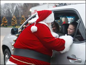 Santa converses with Toledoan Ian Schlatter, whose family dropped off toys.