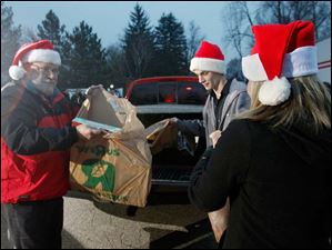 Sylvania resident Robert Smith, left, and Ryan Emch drop off toys during the Hope for the Holidays toy drive at Channel 13 ABC studios in Toledo. Smith's company, Dura Magnetics, collected $1,000 for the toy drive and Smith dropped off the toys bought with that money. They are handing the toys to Ch. 13 reporter Amy Montgomery.