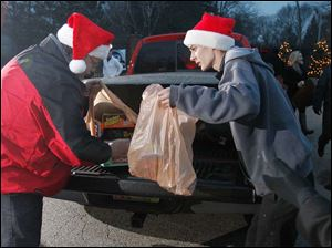 Sylvania resident Robert Smith, left, and Ryan Emch drop off toys.