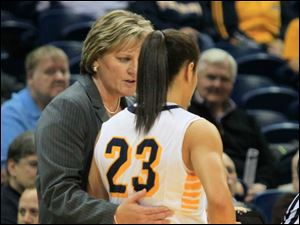 UT coach Tricia Cullop talks with Inma Zanoguera while a teammate shoots a foul shot.