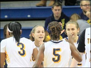 UT teammates #3, Lucretia Smith, left, Naama Shafir, center, and #12, Riley McCormick, congratulate #5, Janelle Reed-Lewis, for her play.
