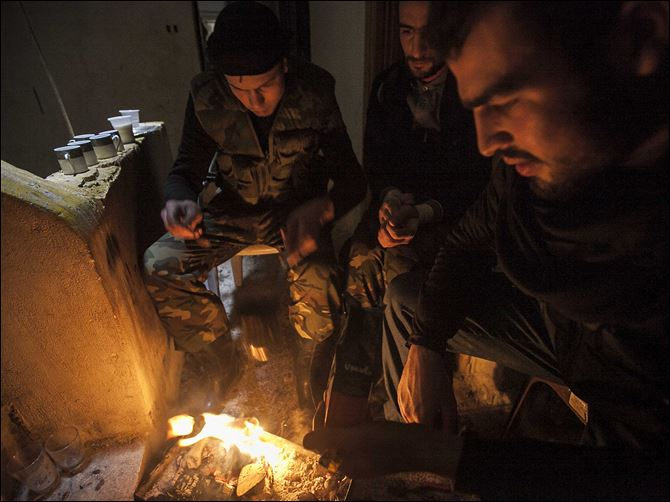 Syrian rebels make a fire to keep warm Syrian rebels make a fire to keep warm after clashes with troops loyal to Syrian President Bashar Assad at on the front line in Aleppo, Syria.