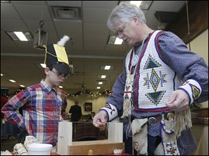 Moline, Ohio, resident Xavier Jackey, 10, watches Brian Jensen work with loom beads.
