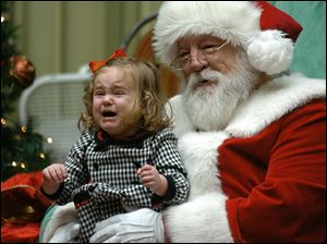 Rose Morrison, 2,  of Scranton, Pa. cries as she sits with Santa Claus for a holiday portrait in Dickson City, Pa.