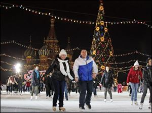 People skate on the ice rink opened on Red Square, with St. Basil Cathedral in the background, in Moscow, Russia