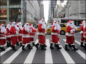 Volunteers of America Santas ring their bells as the cross a street in Fifth Ave. during their 110th annual Sidewalk Santa Parade, in New York, Nov. 23.