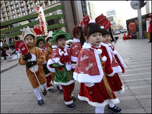 South Korean children wearing Santa Claus outfits leave after attending a ceremony by the Salvation Army to prepare charity pots for a year-end fundraising campaign for the underprivileged in Seoul, South Korea, Nov. 26.