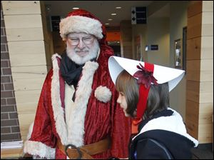 Father Christmas converses with Maumee resident Haley Hughes, 8.