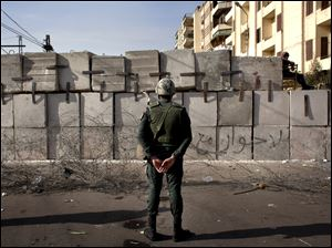 An Egyptian soldier stands guard in front of the presidential palace in Cairo, Egypt.