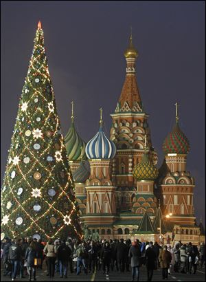 People walk in Moscow's Red Square decorated for New Year and Christmas celebrations, with St. Basil Cathedral in the background.