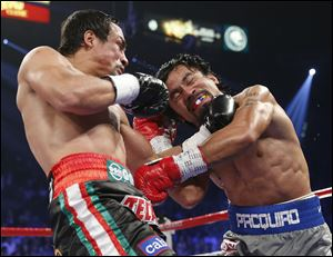Juan Manuel Marquez, left, lands a left hook on Manny Pacquiao during their fight late Saturday night. It was the first win in four fights for Marquez against Pacquiao.