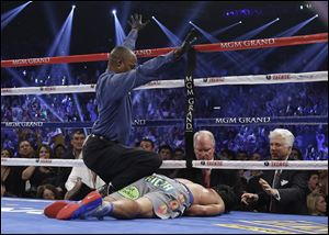 Referee Kenny Bayless calls the fight as he kneels over Manny Pacquiao after he was knocked out by Juan Manuel Marquez during their WBO world welterweight  fight Saturday in Las Vegas.