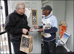 Mobile Meals of Toledo volunteer driver Jim Szymanski delivers a meal bag to Elgin Rogers, at his home Friday in Toledo.
