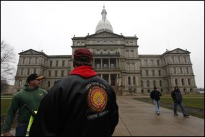 International Brotherhood of Electrical Workers members stand outside the capitol Friday in Lansing. Michigan could become the 24th state with a right-to-work law next week. Rules require a five-day wait before the House and Senate vote on each other's bills; lawmakers are scheduled to reconvene Tuesday and Gov. Rick Snyder has pledged to sign the bills into law.