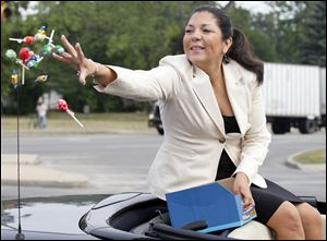 "Lucas County Auditor Anita Lopez throws candy during a parade in July. ""I have not officially announced that I will be running for mayor. But I am seriously considering running,"" Ms. Lopez said last month."