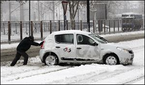 A man pushes a car on a snow covered street in Belgrade, Serbia, Sunday.