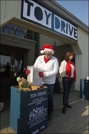 Volunteers Barbara Brotzki, left, and Lisa Harris collect toys for the Noel Project at the Church on Strayer. The Noel Project accepts donations of new, $10 toys.