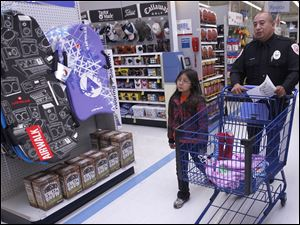 Cygnet, Ohio resident Brooklyn McKee, 7, shops with Owens Community College police officer Luis Munguia during a shopping spree at Meijer in Rossford, Ohio.